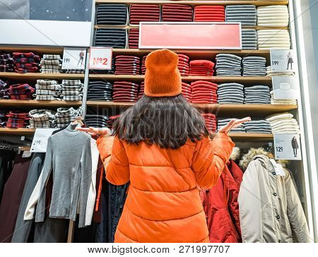 Rear View Of Confused Woman Gesturing Hands To The Side While Looking At Clothes Displayed In Store.
