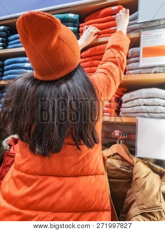 Rear View Of Confused Woman Gesturing While Looking At Clothes Displayed In Store. Lot Sweaters Of D
