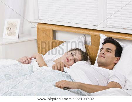 An attractive young couple sleeping in bed together.  They look peaceful.  Horizontally framed shot.