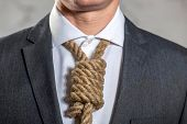 Midsection of businessman with noose used as a tie around is neck whilst wearing suit and shirt, highlighting suicide or demotivation at work or in the office poster