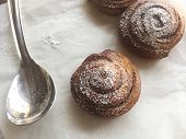 cinnamon buns on a white cloth and a spoon poster