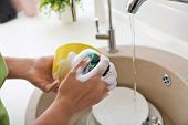 Woman washing dirty dishes in kitchen sink, closeup. Cleaning chores poster