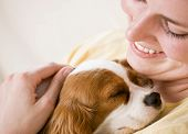 Devoted woman hugging and comforting pet dog poster