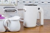 White electric hand-held mixer with two beaters against of different crockery on a cook table poster