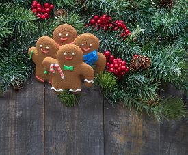 Handmade Gingerbread Cookies With Christmas Tree Branches With Red Berries And Pines On Old Wood Bac