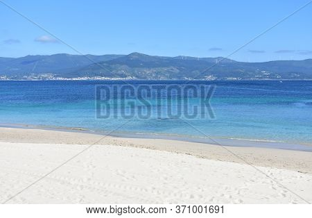 Bay with turquoise water and beach with white sand and blue sky. San Francisco beach, Muros, Galicia, Spain.