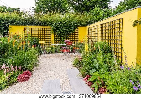 Garden Design With Concrete Yellow Wall And Colorful Flowerbed