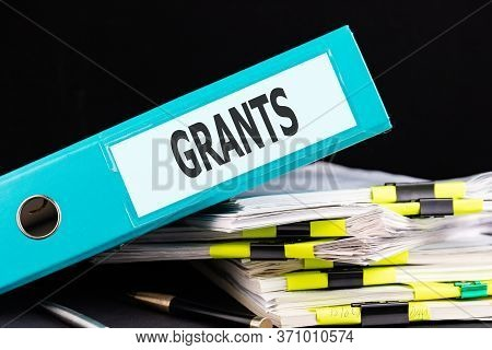 Text Grants Is Written On A Folder Lying On A Stack Of Papers With A Pen On The Table. Business Conc