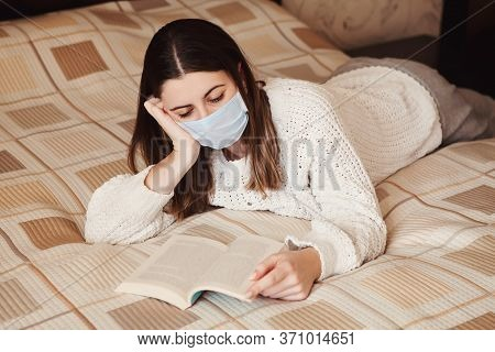Woman Reading Book In Bed Young Woman In Medical Mask Stay Isolation At Home For Self Quarantine Con