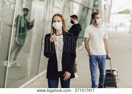 Figures Of Young People In Protective Masks Near The Airport. Safe Travel During A Pandemic. Airplan