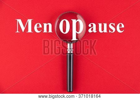 The Word Menopause Through A Magnifying Glass On A Red Background.