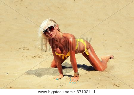 Young beautiful blond woman tanning on sunbed on the beach