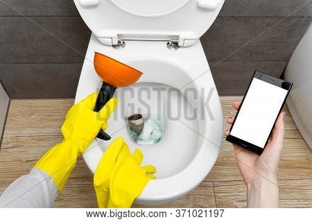 Overflowing Broken Toilet. Clogged Toilet. A Smartphone With A White Screen For Advertising About Pl