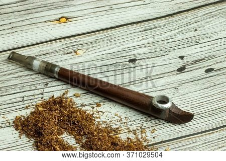 Concept Of The Ritual Use Of Tobacco And Nicotine. Smoking Pipe Close-up With Copy Space