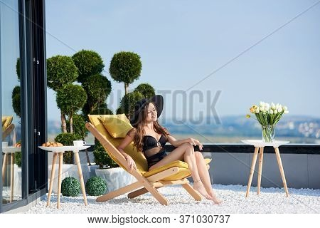 Gorgeous Brunette Female In Black Swimsuit And Hat Is Basking At Sun On Terrace Apartment With Panor