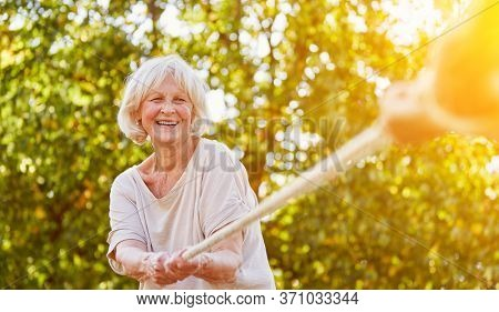 Seniors laughing while tug of war in summer in nature
