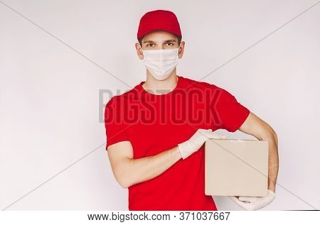 Portrait Young Delivery Service Employee In Red Uniform, Medical Face Mask And Protective Gloves Car
