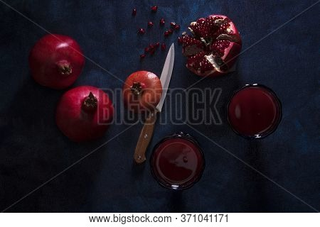 2 Glasses Of Fresh Pomegranate Juice With Few Ripe Real Pomegranates On Dark Blue Background. Partia