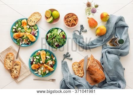 White Wooden Table With Walnut Salad, Caramelised Pears And Feta Cheese. Turquoise Dishes With Salad
