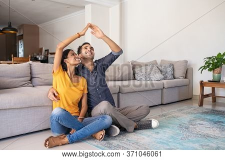 Handsome young man with beautiful indian woman dreaming a new home. Smiling married couple moves to new apartment with copy space. Happy middle eastern couple making roof with hands symbol of new home
