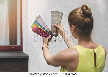 Woman Choosing Paint Color For House Exterior Facade