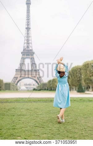 Back View Of Pretty Lady In Blue Dress And Hat, Enjoying Walk In Paris, Near Eiffel Tower. Young Att