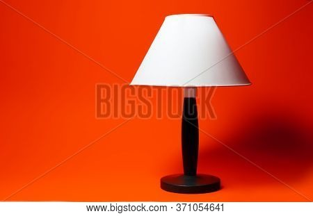 Close-up Of Night Lamp With White Shade And Black Tripod On Background Of Lush Lava Color.