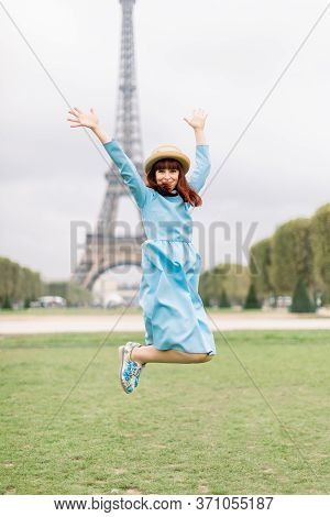 Portrait Of Pretty Fashion Young Red Haired Woman In Blue Dress, Having Fun And Jumping In Front Of
