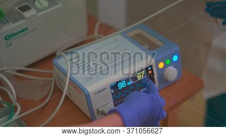 Pulse Oximeter. Nurse In Blue Disposable Gloves Shows Explains The Operation Of Medical Equipment. M