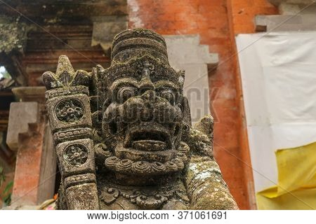 A Close Up On A Guardian Figure Next To A Hindu Temple On Bali, Indonesia. A Bricked Entrance Gate T