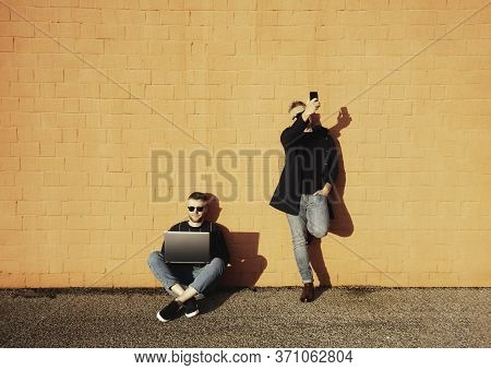 Two Friends Or Colleagues With Digital Devices During Lunch Break - Young Caucasian Man Sitting Cros