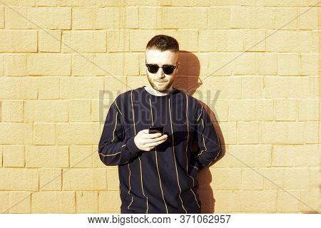 Guy In Casual Wear With Mobile Phone - Young Caucasian Man Standing At Outdoor Red Wall And See Vide