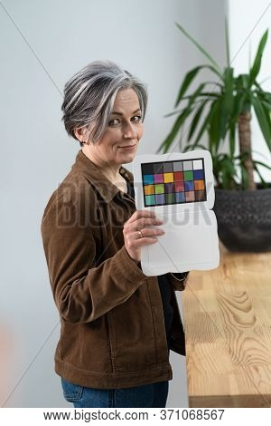 Pretty Woman Holds Color Checker Or Special Target For Color Adjustment While Standing In Office Int