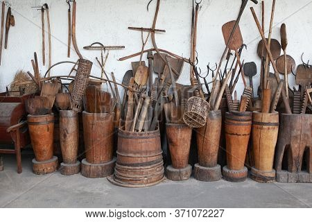Many Different Old Things Household Items: Spinning Wheel, Stupas, Shovels.