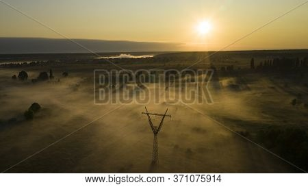 High Voltage Electricity Transfer Lines And Pylon In A Fog