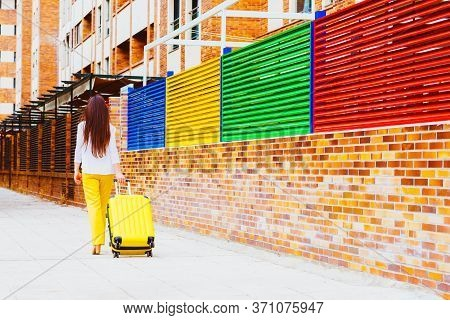 Woman On Her Back With A Yellow Suitcase Walking Down The Street