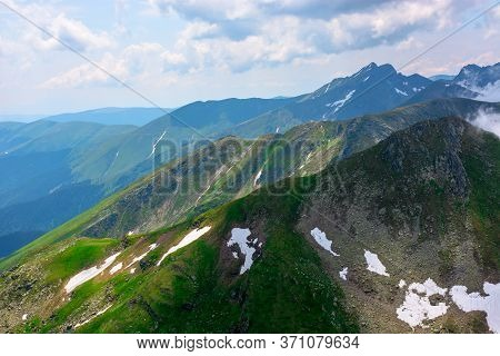 Stunning Landscape In High Mountains Of Romania. Grass And Spots Of Snow On The Slopes. Rocky Peak I