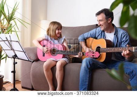 Father And Daughter Playing Guitar In The Living Room Looking At Each Other Smiling With Complicity