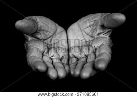 Old wrinkled lady hands with open palms isolated on black background. Begging and poverty concept