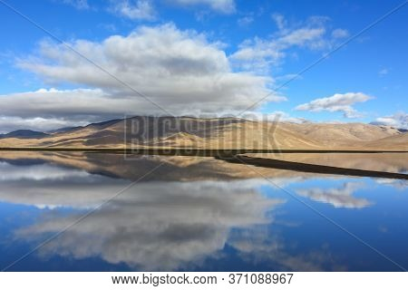 Beautiful Reflection Of Hills And Clouds In Glass Like Waters Of Lake In Tibet, Asia