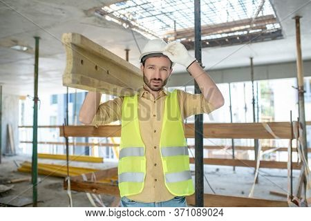 Tired Building Worker In Yellow Vest And Gloves Carrying Wooden Board On His Shoulder, Touching Helm