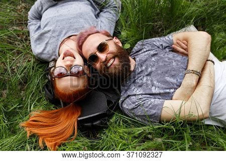 Smiling Couple, Seated Down On A Green Grass, In Park, Seated Down In Sunglasses, Looking At Camera.