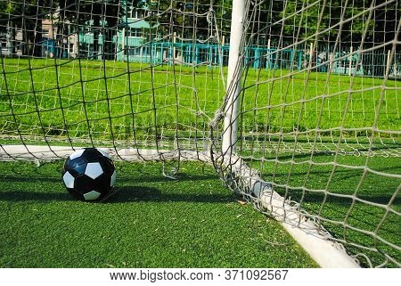 Black Soccer Ball In Goal Net On A Green Lawn On A Sunny Summer Day. The Goal Net Is Dirty And Torn.