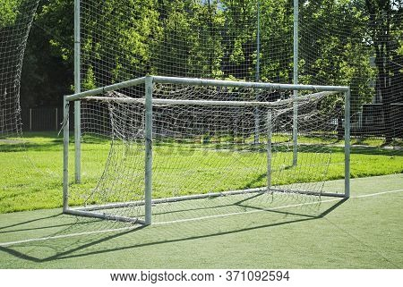 Soccer Goal On A School Soccer Field On A Sunny Summer Day. Amateur Football, Goal With A Torn And D