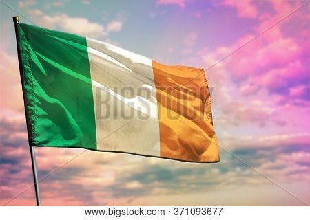 Fluttering Ireland Flag On Colorful Cloudy Sky Background. Ireland Prospering Concept.