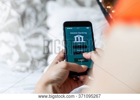 Young Woman Using Mobile Banking App In Her Quiet Room, Zenithal Plane, Concept Of Using The Bank Wh