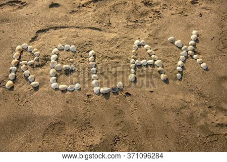 The Word Relax Is Laid Out With Shells On The Sand.