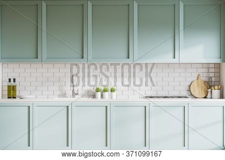 Interior Of Stylish Kitchen With White Brick Walls, Blue Cupboards And Countertops With Built In Sin