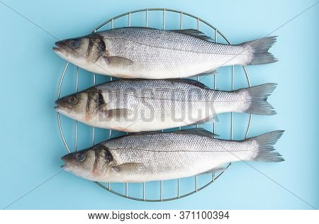 Three Fresh Sea Bass On The Grill On A Blue Background. Natural Sea Fish, Healthy Nutrition, Mediter