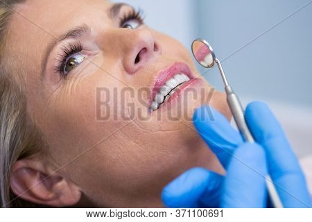 Close up of doctor holding angled mirror by woman at medical clinic